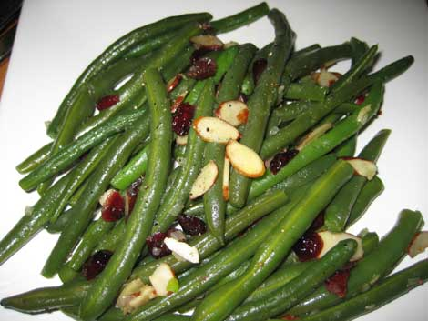 Greenbeans with sliced almonds and cranberries on a white plate