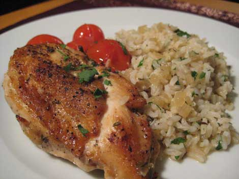 Wine-braised chicken with cherry tomatoes and herbed brown rice on a right plate