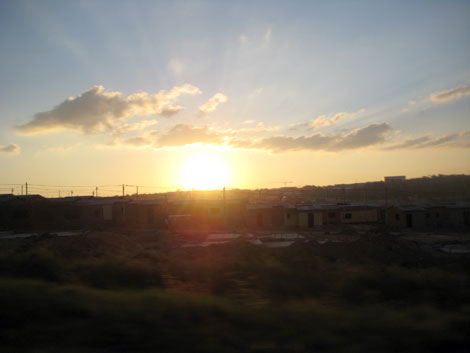 Rising sun in the background of a row of South African shanty houses.