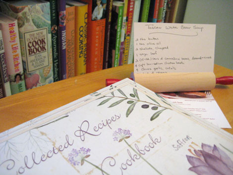 Notebook titled Collected Recipes Cookbook with two recipe note cards on a table in front of a bookshelf full of cookbooks