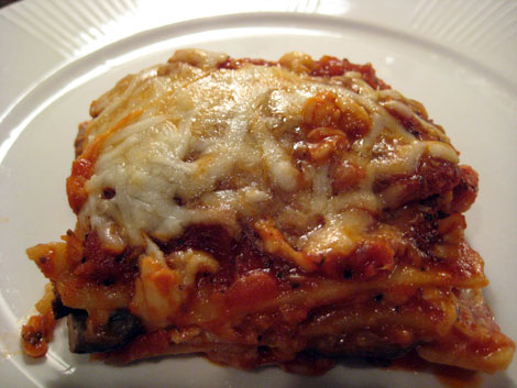 Square portion of lasagna on a white plate