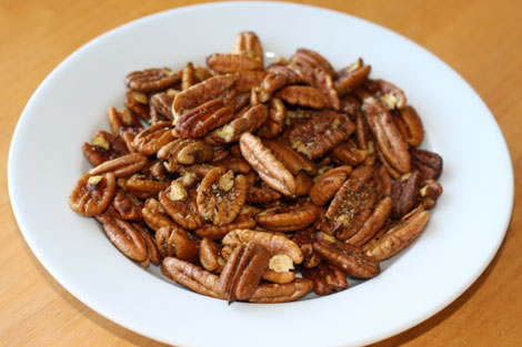 Image of curry spiced pecans in a white bowl on a light brown table