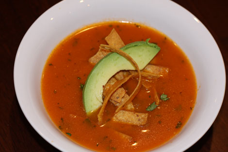 White bowl of tortilla soup on a dark brown wooden table. Soup is garnished with tortilla strips and a slice of avocado