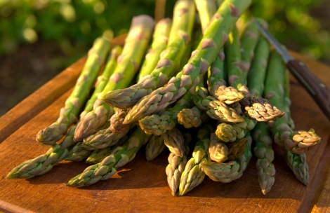 Fresh picked asparagus on a cutting board outside in the sun.