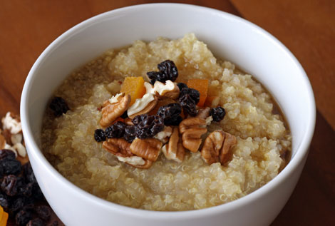 Bowl of warm quinoa-millet cereal with dried currants and apricots, and chopped pecans with maple syrup all in a white bowl sitting on a brown wooden table.