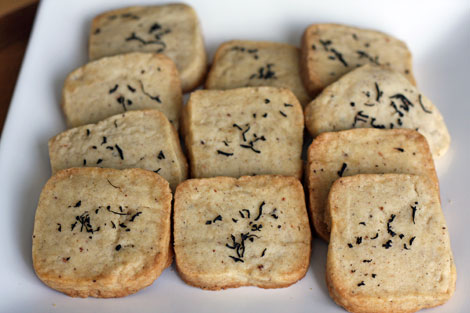 Square chai spice cookies sprinkled with black tea leaves on a white plate