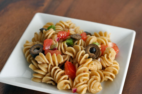 Corkscrew wholegrain pasta salad with diced tomatoes, sliced black olives, scallion greens and vinaigrette - small serving on a square white dish on a brown table.