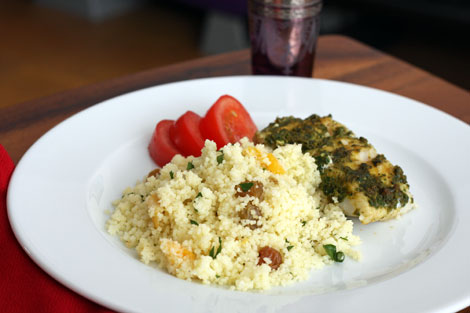 Plate of couscous (golden raisins and apricots) with chermoula marinated halibut and sliced tomatoes