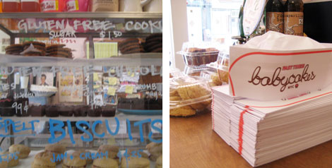 Image 1: A case in Babycakes NYC bakery of gluten free, vegan chocolate-chip and double chocolate cookies, and spelt biscuits; Image 2: Photo of a stack of paper Babycakes NYC hats (old-school diner style hats) and packaged vegan desserts all sittin gon a table in front of a window