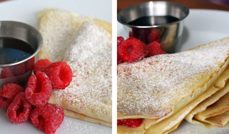 Folded crepes with raspberry filling and topped with powdered sugar on a white plate with maple syrup in a small stainless steel cup.
