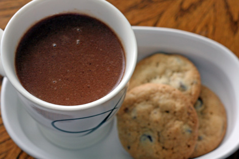 A white mug of hot chocolate on a white plate with three chocolate chip cookies