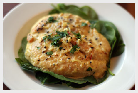 Chicken Scallopine in a saffron, mustard seed and cumin cream sauce over a bed of fresh baby spinach all on a white plate