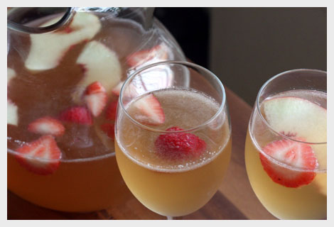 Glass pitcher of white peach sangria with two wine glasses full of sangria with strawberries and peach slices.